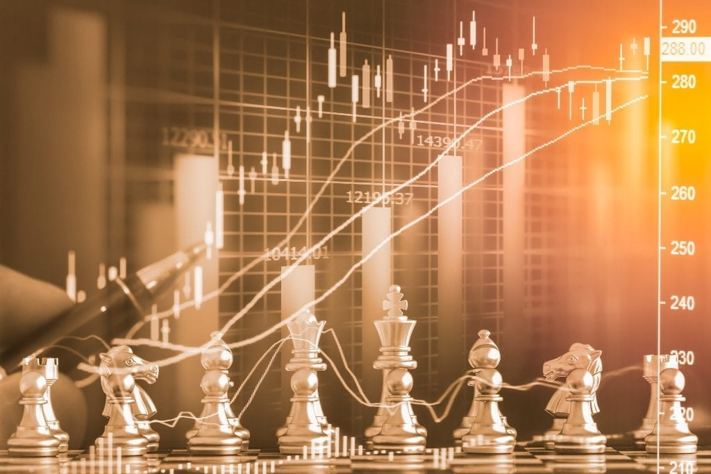 Gold chess pieces in front of Forex chart