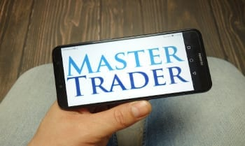 Man holding phone with master trader image