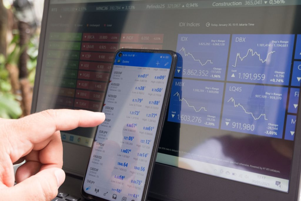 Trading currency with phone and laptop